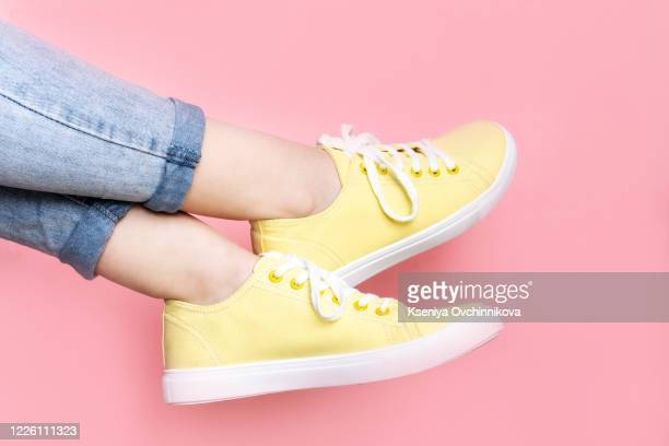 woman in stylish sneakers near color wall, closeup. space for text - womens pretty feet stock pictures, royalty-free photos & images