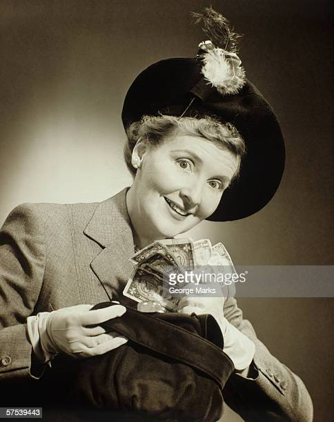 Woman in suit and fashionable hat standing taking money out of bag in studio, (B&W), portrait
