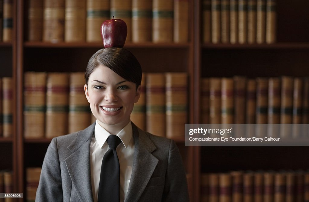 woman in suit balancing red apple on head : Stock Photo