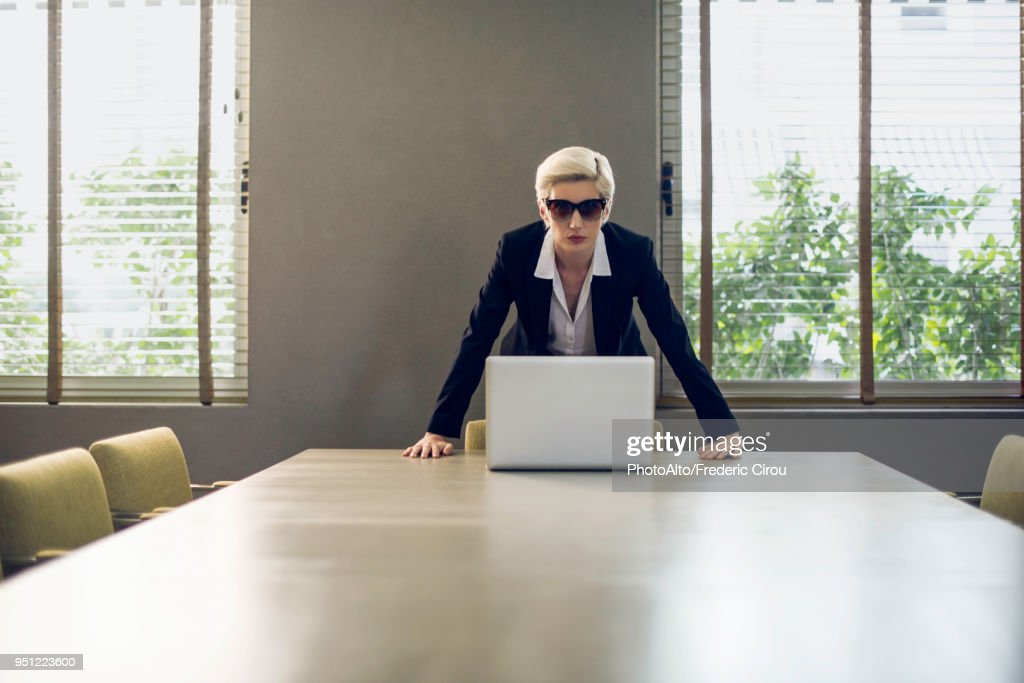 Woman in suit leaning against table looking at camera : Photo