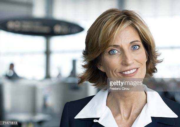 woman in suit smiling in airport setting, portrait - cuello parte de la vestimenta fotografías e imágenes de stock