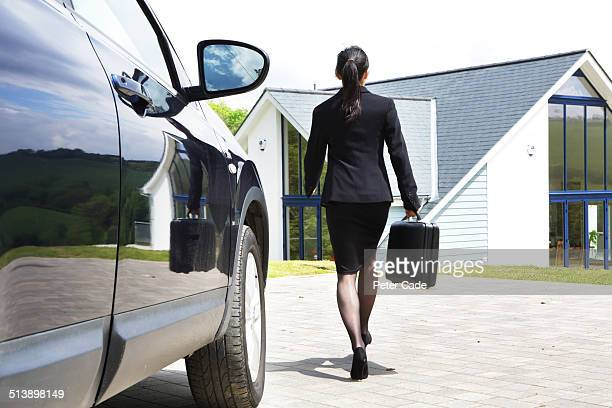 Woman in suit walking from car to house