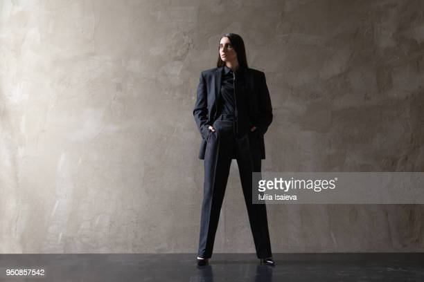 Woman in suit with hands in pockets