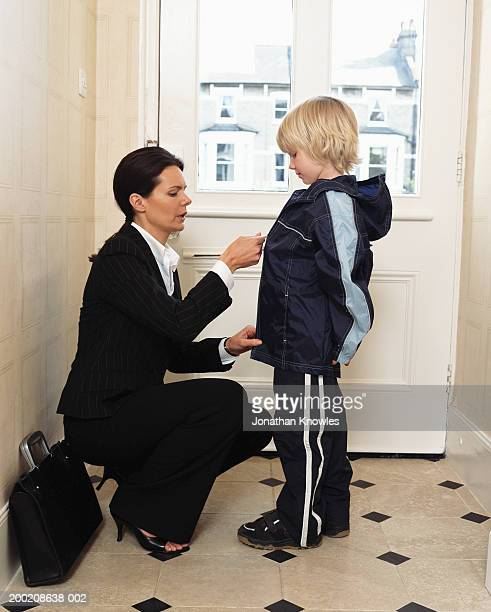 Woman in suit zipping up son's (5-7) jacket at front door, side view