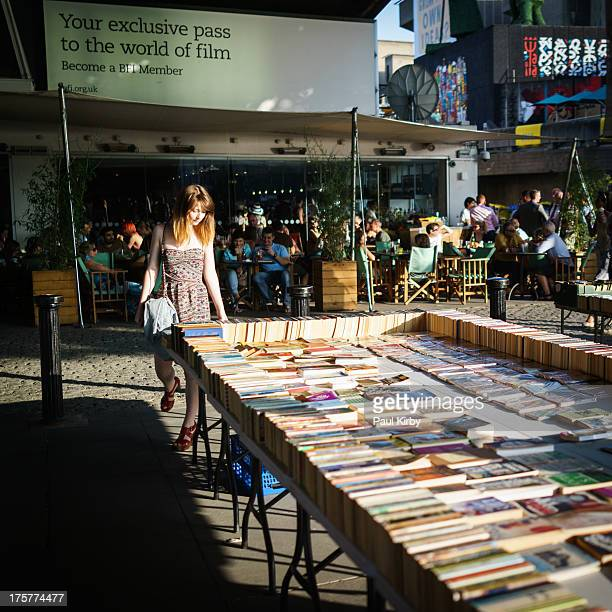 Woman in summer dress browsing books at the Southbank book stall on the Thames Embankment London 2013. Evening sunlight. Cafe Bar in the background.