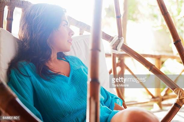 Woman in summer dress relaxing on bamboo swing