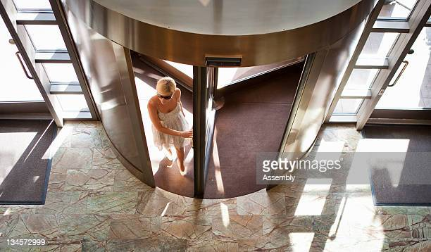 Woman in sun dress walks into hotel lobby.