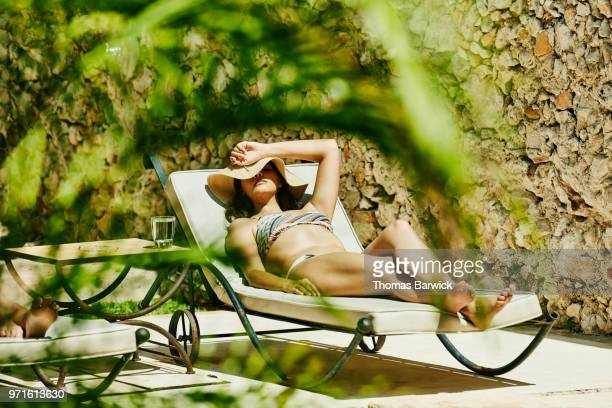 Woman in sun hat relaxing in lounge chair by pool enjoying the sun