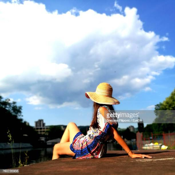 Woman In Sun Hat Sitting Against Cloudy Sky During Sunny Day