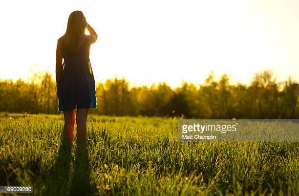 Woman in Sundress Standing in Lush Green Field