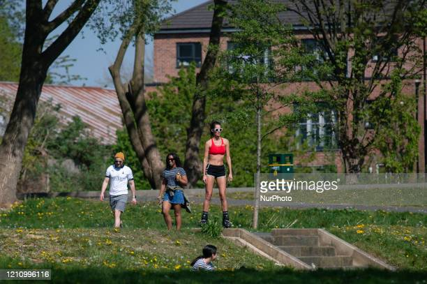 Woman in sunglasses and rollerblades keeps socially distanced and enjoys the sunshine in Peel Park, Salford, Greater Manchester on Saturday 25th...