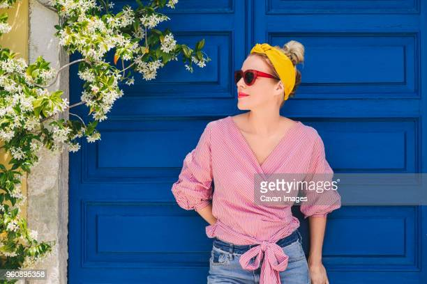 woman in sunglasses looking away while standing against door - headband stock pictures, royalty-free photos & images