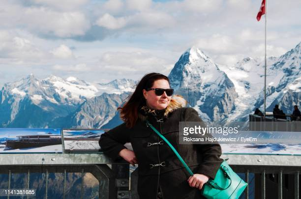 Woman In Sunglasses Standing Against Snowcapped Mountains