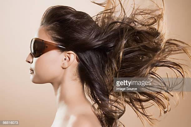 女性のサングラスと吹きさらしの髪