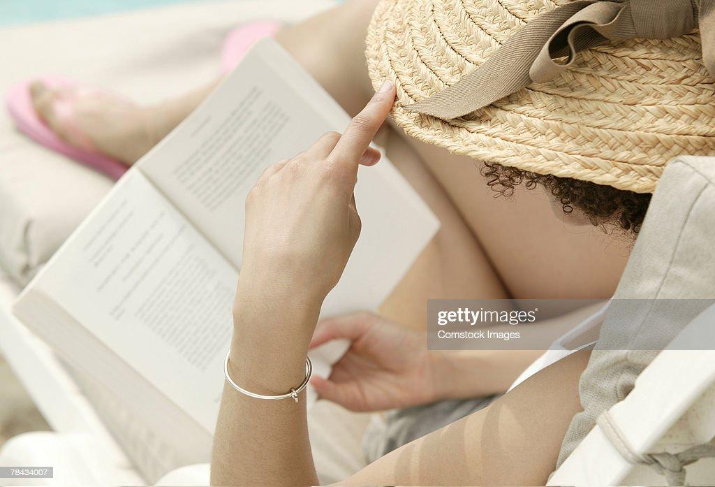 Woman in sunhat reading : Stockfoto