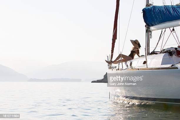 woman in sunhat sits at bow of yacht - yate fotografías e imágenes de stock