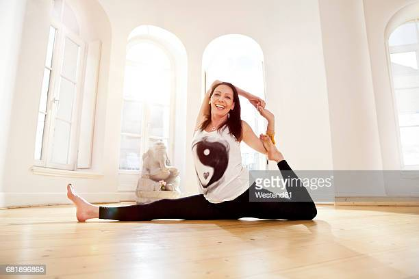 woman in sunny yoga studio getting into parivrrta janu sisasana pose - doing the splits stock pictures, royalty-free photos & images