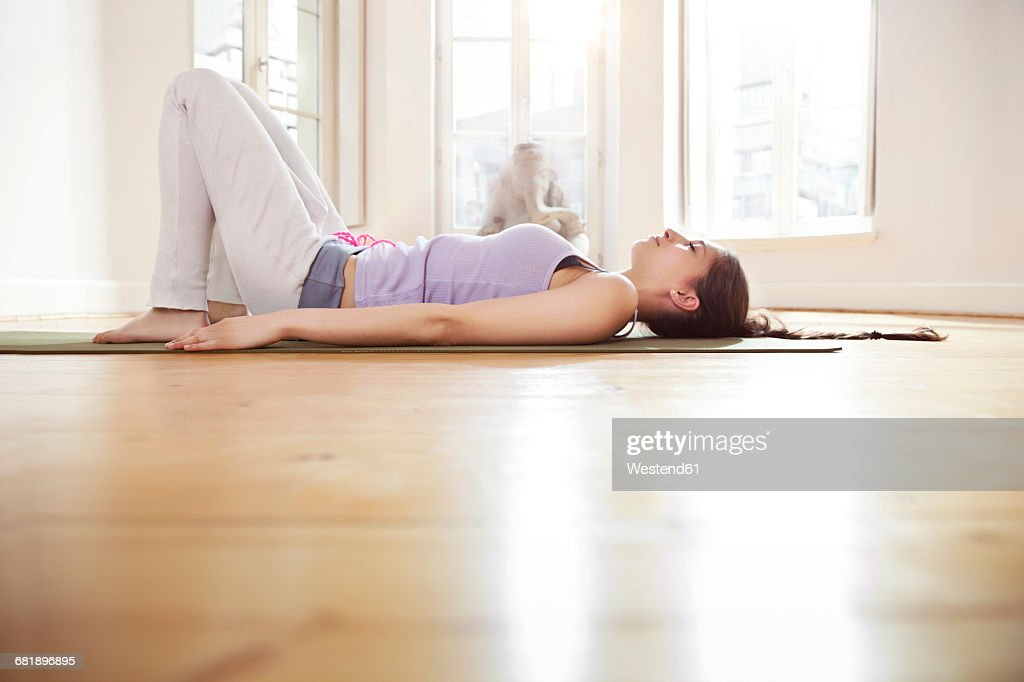 Woman in sunny yoga studio relaxing on her mat : Stock Photo