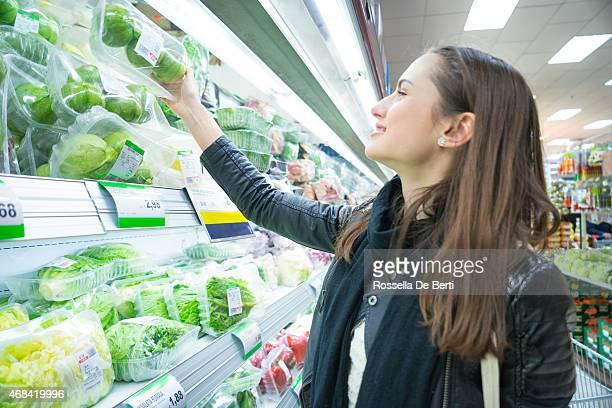 Donna In supermercato Shopping al verdura scaffale