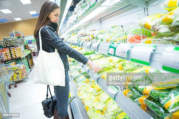 Woman In Supermarket At Vegetable Shelf Shopping