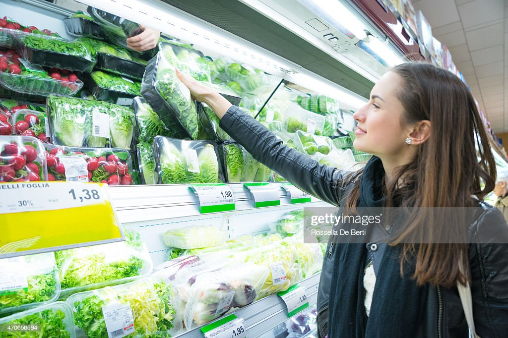 Woman In Supermarket At Vegetable Shelf Shopping : Stock Photo