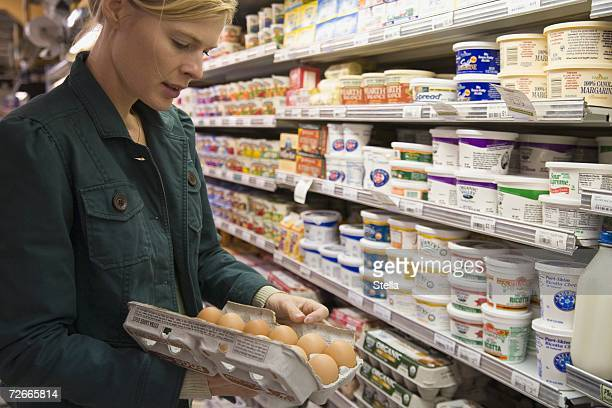 Woman in supermarket examining eggs