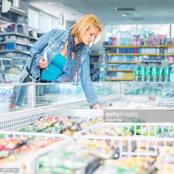 Woman in supermarket near frozen food