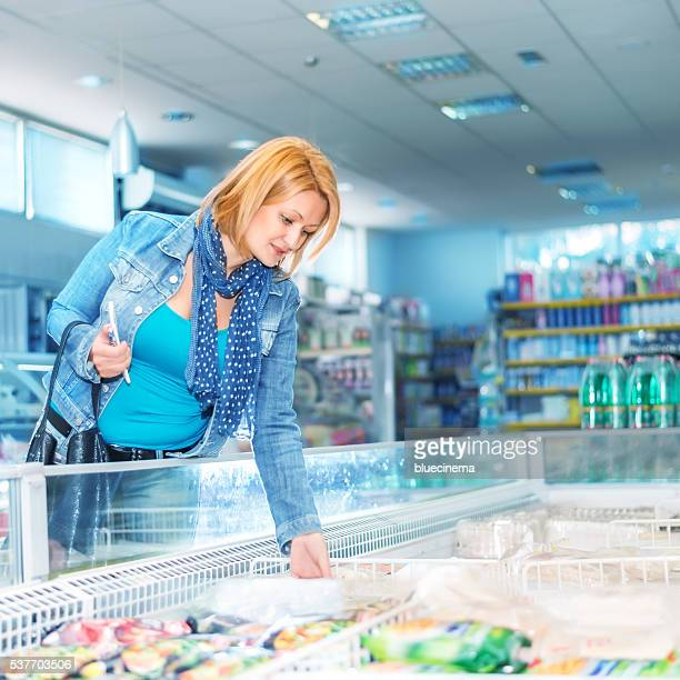 Woman in supermarket near frozen food