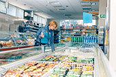 woman supermarket near frozen food