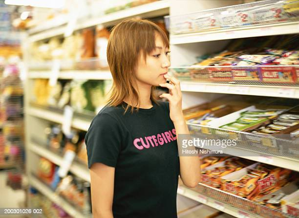 woman in supermarket - convenience store interior stock photos and pictures