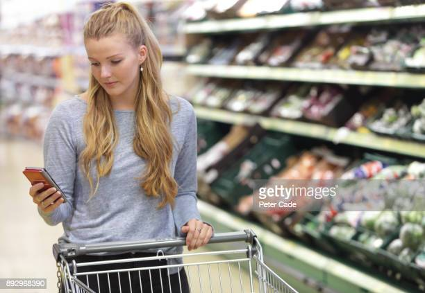 woman in supermarket with trolley, looking at phone - list stock pictures, royalty-free photos & images