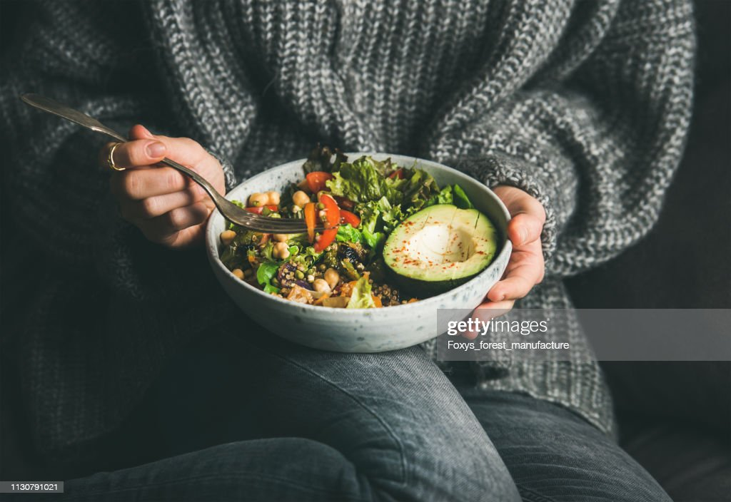 Woman in sweater eating fresh salad, avocado, beans and vegetables : Stock Photo