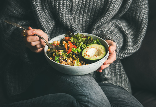 Woman in sweater eating fresh salad, avocado, beans and vegetables 1130791021