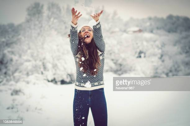 woman in sweater playing snow ball fight in winter - traditionally norwegian stock pictures, royalty-free photos & images