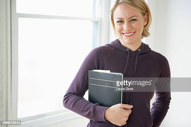 Woman in sweatshirt holding a notebook