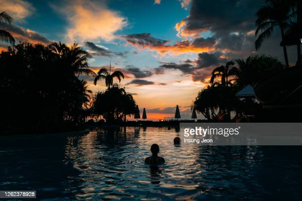 woman in swimming pool at sunset - travel destinations stock pictures, royalty-free photos & images