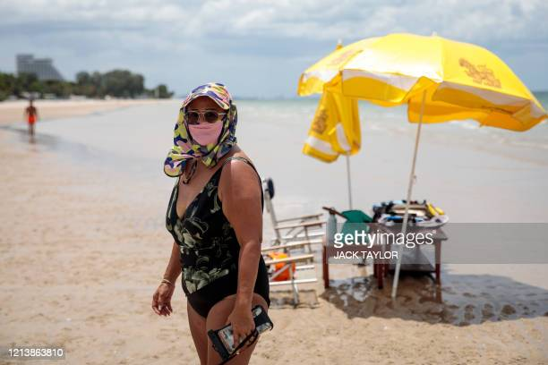 Woman in swimsuit and wearing a face mask, amid concerns over the spread of the COVID-19 coronavirus, walks along Hua Hin beach in Thailand on May...