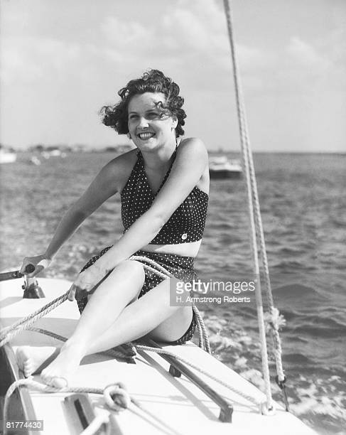 woman in swimsuit, on sailing boat, holding rope, smiling. (photo by h. armstrong roberts/retrofile/getty images) - voilier noir et blanc photos et images de collection
