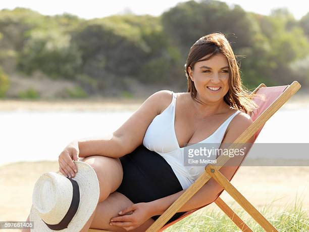 woman in swimsuit sitting on beach chair, point impossible, victoria, australia - large build stock photos and pictures