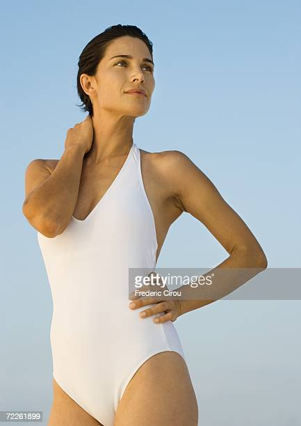Woman in swimsuit standing, looking away