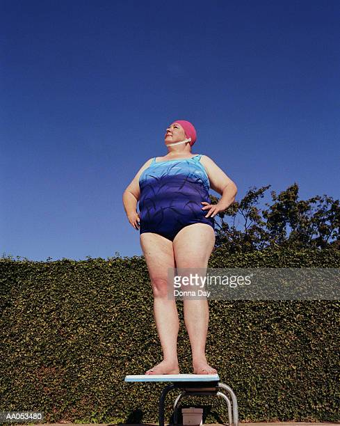 Woman in swimsuit standing on diving board, low angle view