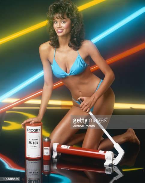 Woman in swimwear holding hydraulic pump smiling portrait