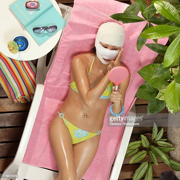 Woman in swimwear with face wrapped in gauze