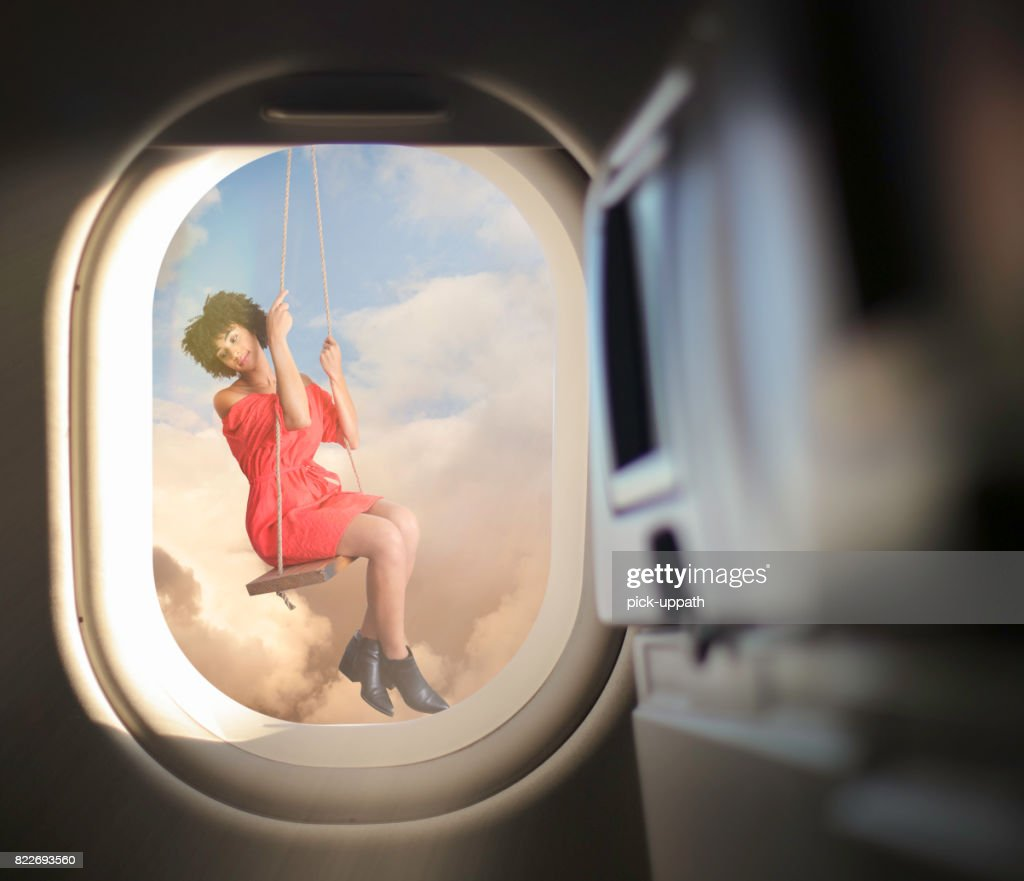Woman in swing outside airplane window : Stock Photo