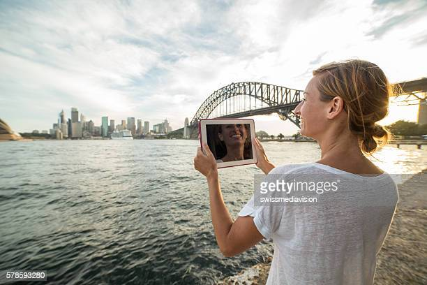 woman in sydney uses digital tablet to photograph sydney skyline - nl ebook stock pictures, royalty-free photos & images