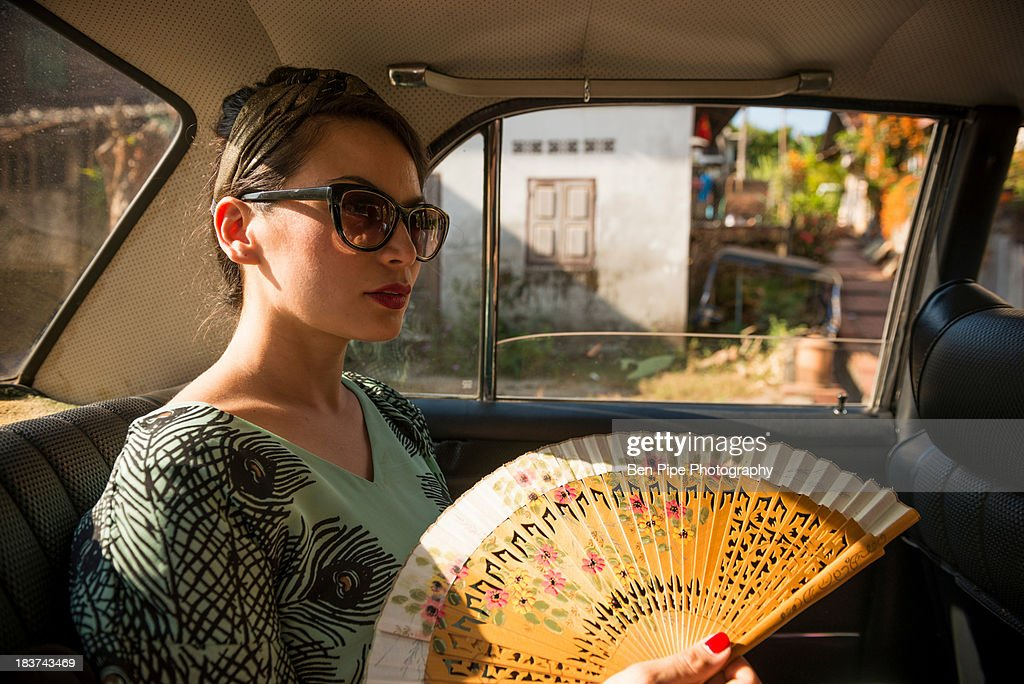 Woman in taxi holding fan : Stock Photo