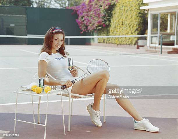 Woman in tennis outfit holding drink can, smiling, portrait
