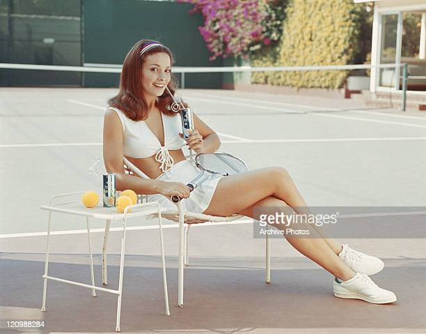 Woman in tennis outfit sitting on chair, smiling, portrait