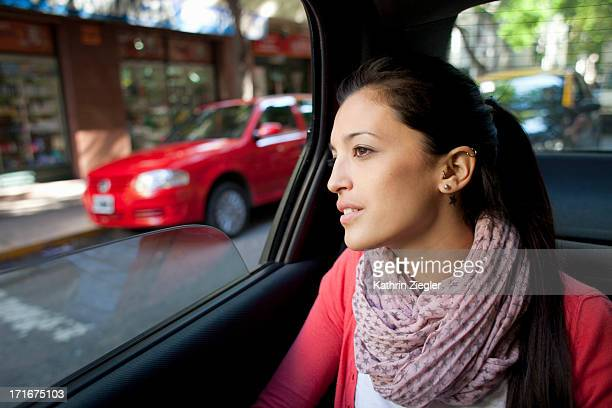 woman in the back of a car, looking out the window