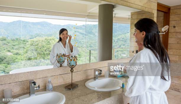 Woman in the bathroom applying cream and looking in the mirror